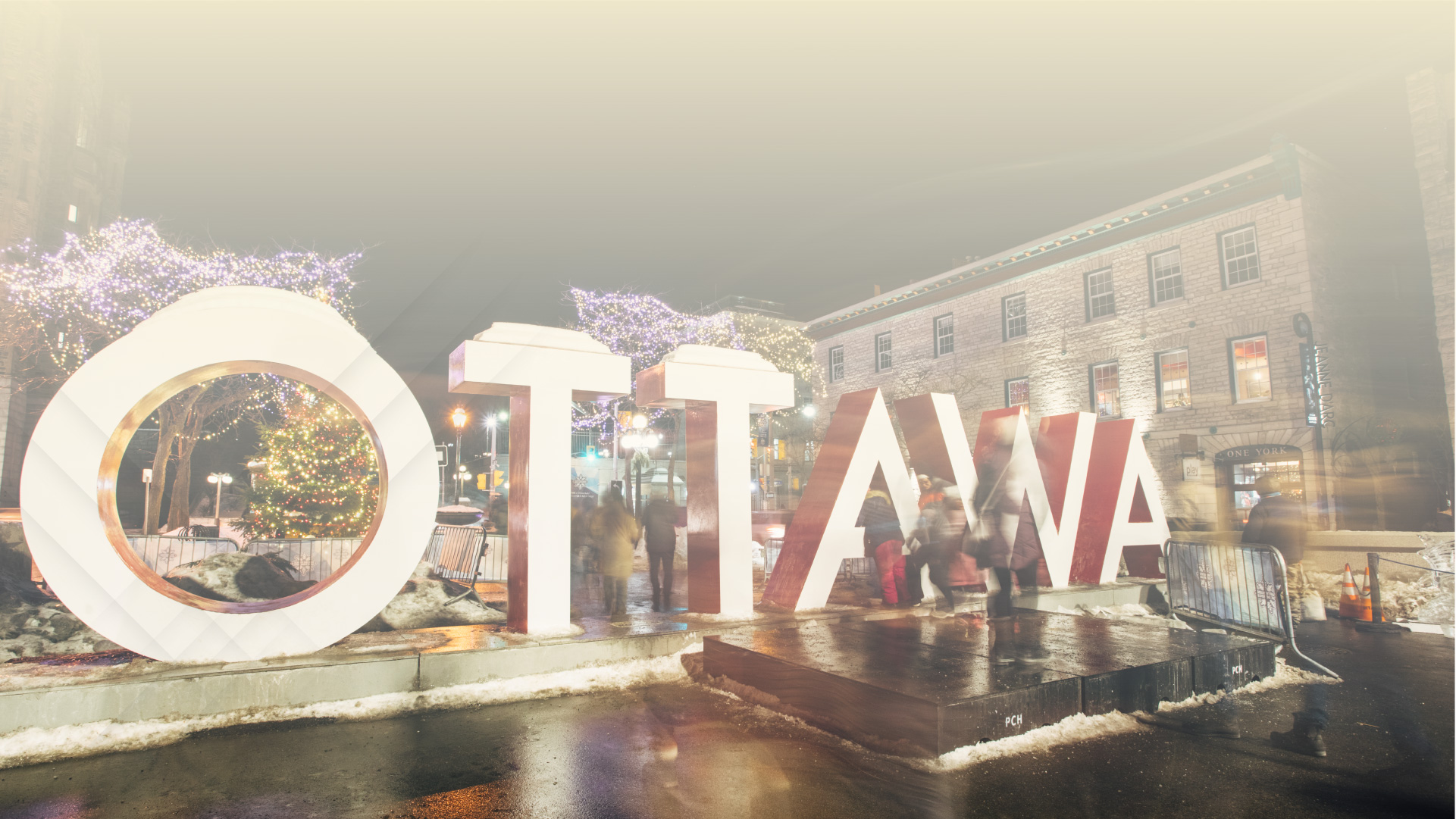 People walking around the Ottawa sign in downtown during the winter