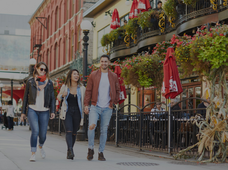 three young adults walking in front of a restaurant in Ottawa's ByWard Market