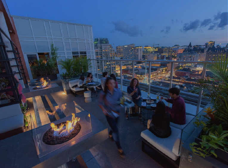 three young professionals having drinks on a rooftop restaurant patio overlooking downtown Ottawa