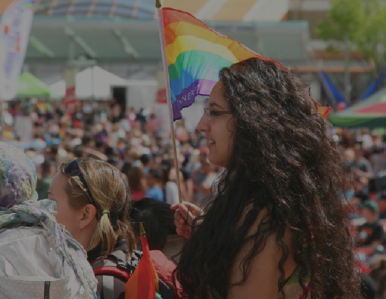 a large festival crowd with a young woman holding a Pride flag