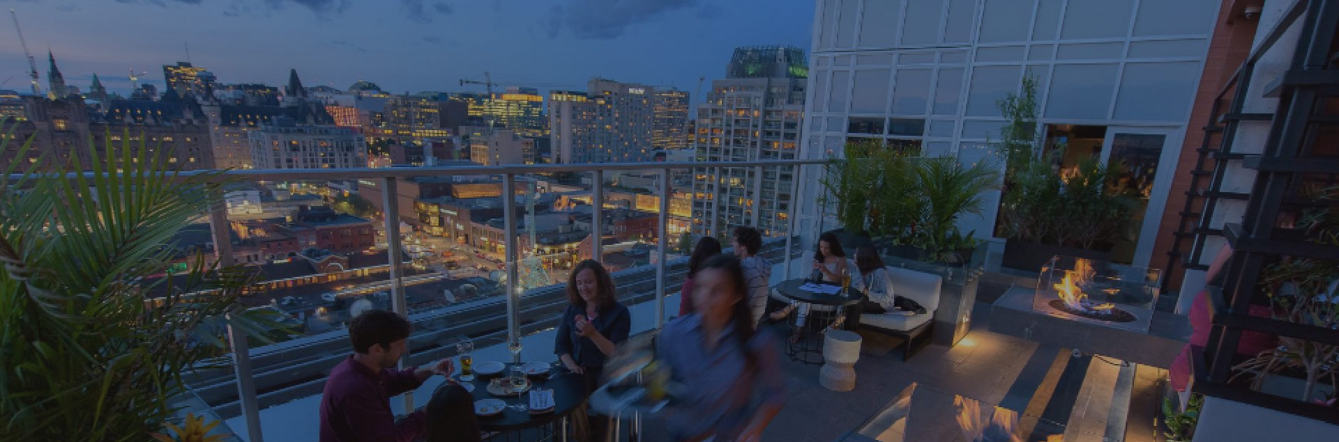 young adults enjoying a meal on a rooftop restaurant patio overlooking Ottawa