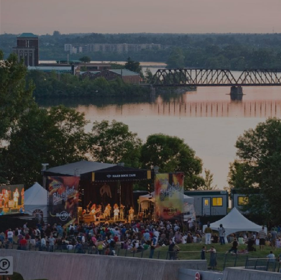 An outdoor music festival with band on stage. River and bridge in background.
