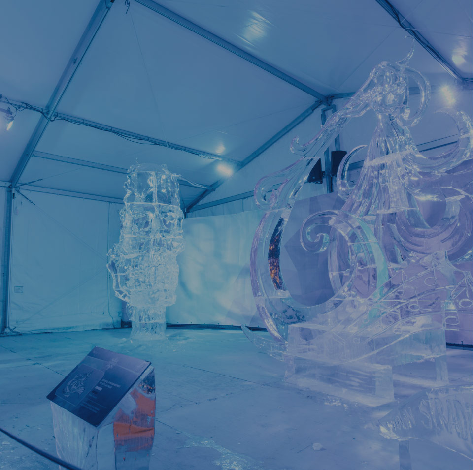 Two ice sculptures under a white tent.